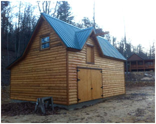 A Log-Sided Country Garage - This customized version of Don Berg's Ashokan Barn design is the garage for a log home in the woods of Alabama. Building plans are available for $35.00 at BackroadHome.net